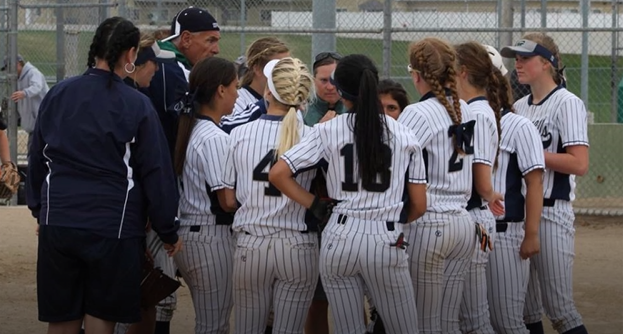 Girls softball team huddled for game strategy.